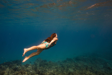 Woman swimming underwater, Oahu, Hawaii, USA