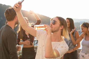 Young man taking selfie drinking beer at waterfront roof terrace party, Budapest, Hungary