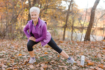 Senior woman exercising in autumn park