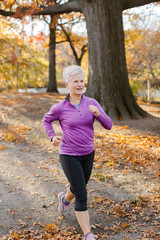 Senior woman exercising, running, in rural setting