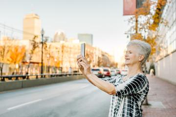 Senior woman outdoors, using smartphone, smiling