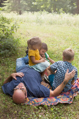 Father and children relaxing on blanket on grass