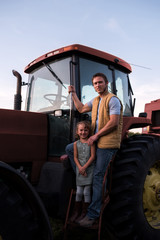 Portrait of father and daughter beside tractor