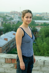 Young happy woman standing on roof over city background