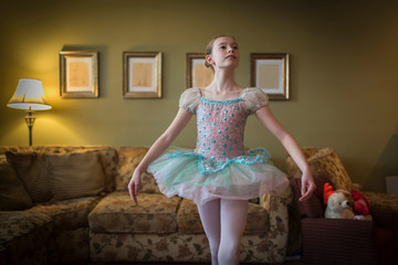 Young girl practising ballet moves in living room