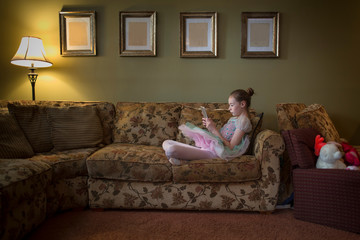 Young girl sitting crossed legged on sofa reading