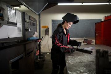 Female metalsmith examining metal rod at workshop bench