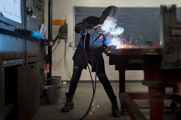 Female metal worker welding at classroom workbench