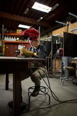 Female metalsmith preparing metal rods at workshop bench