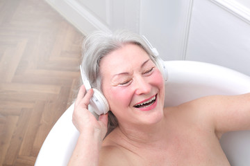 Senior woman smiling and listening to music in bath tub