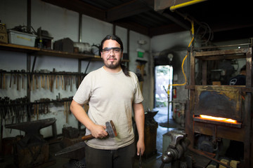 Portrait of male metalsmith by metal workshop furnace