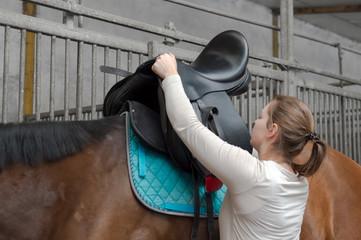 Frau sattelt Pferd mit Sattel aus Leder