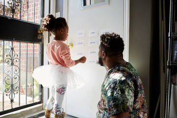 Girl in tutu with father reading words on wall