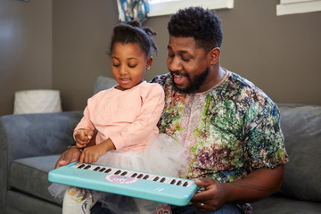 Girl on sofa with father playing toy keyboard