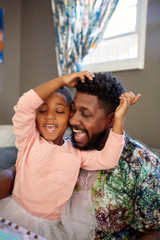 Girl and father singing together in living room