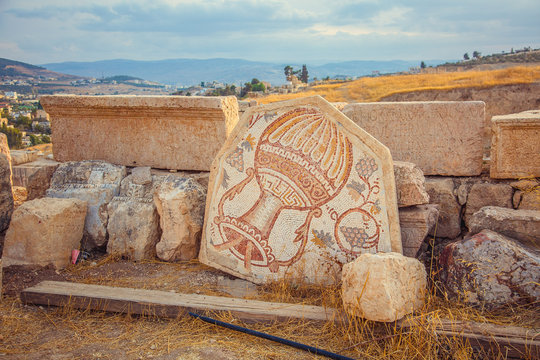 An old Roman mosaic with wine jar and grape in city of Jerash, Jordan