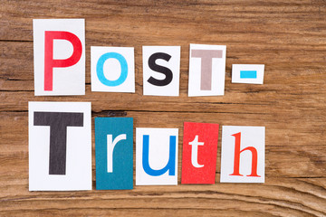 "Phrase ""Post-Truth"" in cut out magazine letters on wooden background"