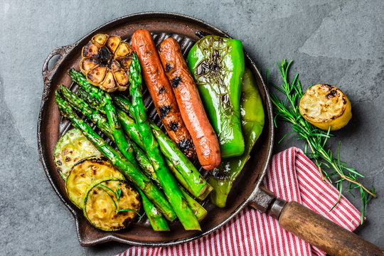 Grilled vegetables and sausages on cast iron grill pan. Gray slate background.