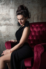 attractive woman sitting in a velvet armchair