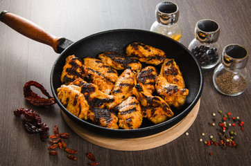 grilled chicken wings in grill panwith spices, wooden background