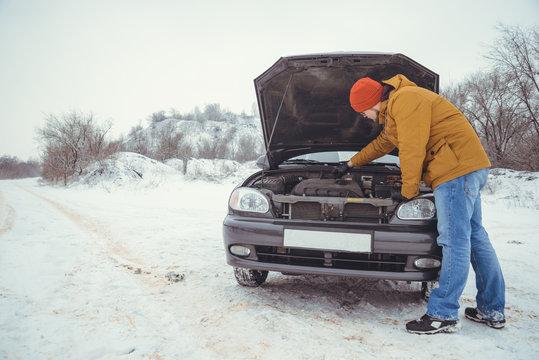 upset young men looking under the hood