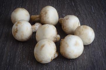 Fresh mushrooms champignons on wooden background.