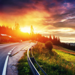 Fantastic sunset that leads into the mountains. Asphalt road wit