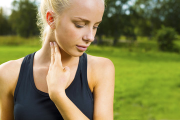 Blonde woman checks her pulse after a long run