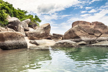 Tropical beach with big round rocks in tranquil transparent sea and blue vibrant blue sky