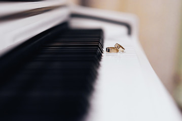 Two gold wedding rings lying on the piano keys