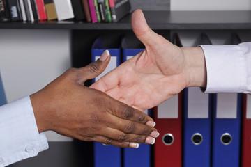 poignée de main homme blanc caucassien et femme noire dans un bureau