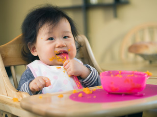 baby girl eating mashed sweet potatoes