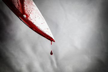 close-up of man holding knife smeared with blood and still dripping. - fototapety na wymiar