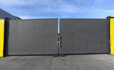Industrial yard security gate under blue sky. horizontal.