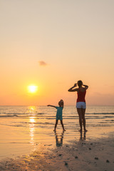Happy mother and young daughter on the beach at sunset.