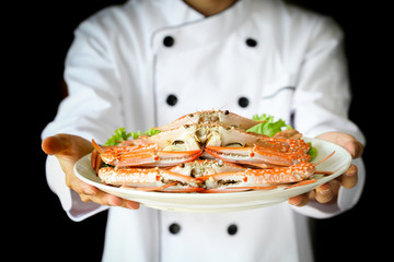 Chef proudly presenting steamed crabs on the plate in dark dramatic background