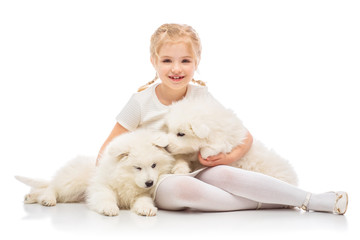 Little girl with a samoyed puppies