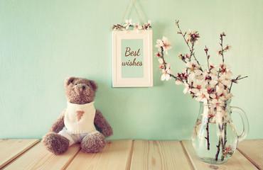 cute teddy bear sitting next to spring cherry tree