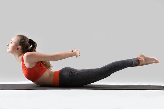 Young attractive woman practicing yoga, stretching in Double Leg Kicks exercise, Salabhasana pose, working out, wearing sportswear, red sports bra, pants, full length, isolated, grey studio background
