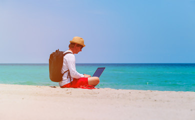 remote work -man with laptop on beach