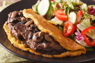 Imperial beef steak with mushrooms, scrambled eggs and vegetable salad close-up. horizontal