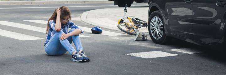Car accident victim sitting on a street