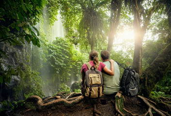 Couple hikers with backpacks enjoying view waterfall in rain forest