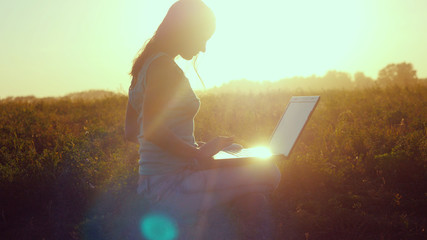 Young beautiful woman typing on a laptop outdoors at beautiful sunset sitting on the grass with amazing lense flare effects
