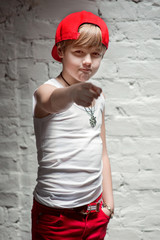 Portrait of cool young hip hop boy in red hat and red pants and white shirt in the loft
