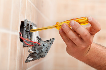 Electrician testing for electricity in electrical wall fixture