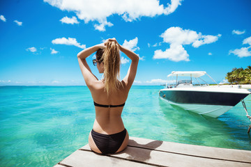 Back view of young lady in black bikini holding hair in ponytail looking at yachts.