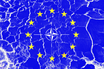 European union and Nato organization flag painted on torn cracked background.