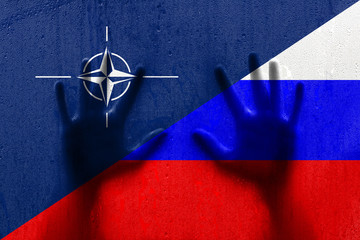 Wet rainy textured Nato and Russian flag with human hands. Conceptual relationship background.