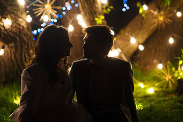 wedding couple in magical night forest decorated light garlands silhouette